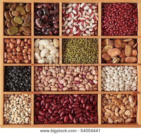 Different beans in wooden box close up