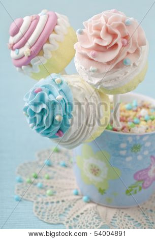 Colorful cupcake pops on blue background