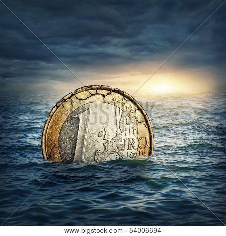 Euro coin sinking in water. Euro crisis concept.