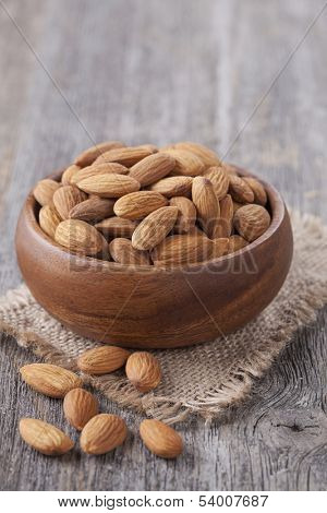 Bowl with almonds nuts on wooden table