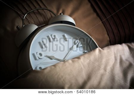 Alarm clock in bed concept for bed time, asleep, sleeping or insomnia
