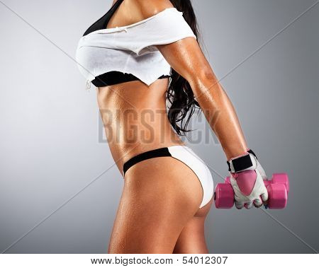 Young woman doing exercise with dumbbells in sexy sportswear