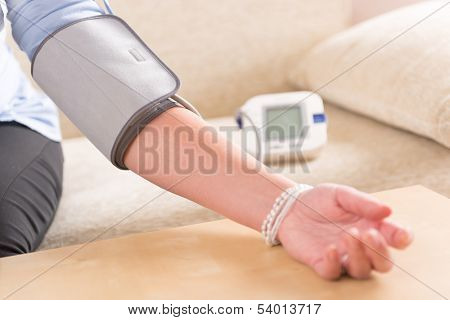 Women's hand with blood pressure monitor cuff
