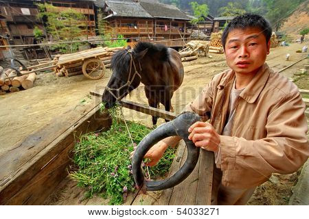 Asian Village, Rural Chinese Peasant Farmer Is Holding Horse-collar.
