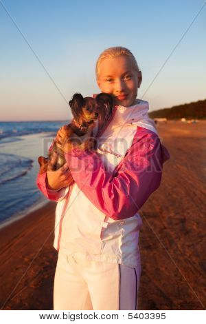 Young Beautiful Woman With Her Dog On A Beach
