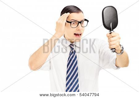 Young worried man checking for thinning hair in the mirror isolated on white background