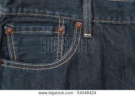 A blue jean pocket with rivets and a waistband used as a background