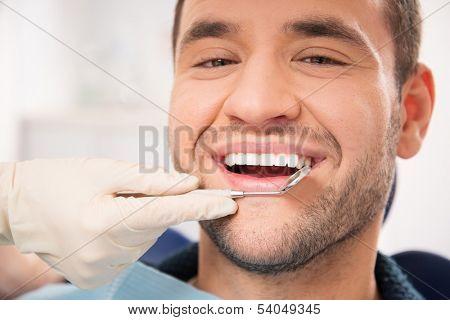Handsome smiling man at doing checkup at dentist's surgery