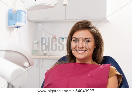 Beautiful young brunette woman visiting dentist