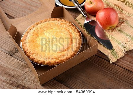 Closeup of a fresh apple pie in a bakery box on a rustic wood table. A plate, serving utensil and fresh Fuji apples are in the background. Horizontal format.
