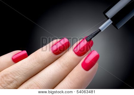 Beautiful manicure process. Nail polish being applied to hand. Black backgrou