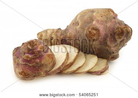 bunch of topinambur roots (helianthus tuberosus) and a cut one on a white background