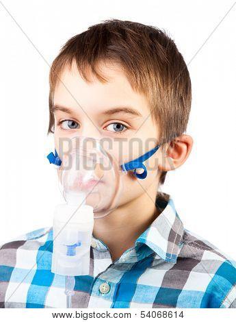 Portrait of cute boy using nebulizer on white background