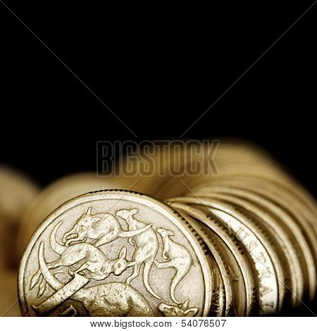 Australian one dollar coins over black background.