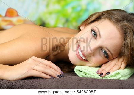 Beautiful young woman on massage table on natural background