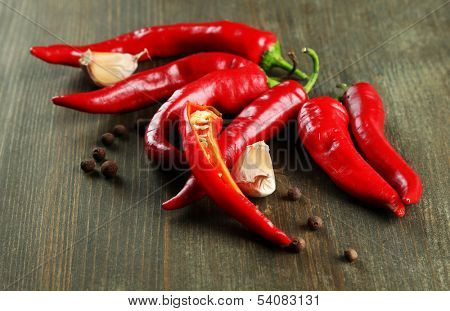 Red hot chili peppers  and garlic, on wooden background