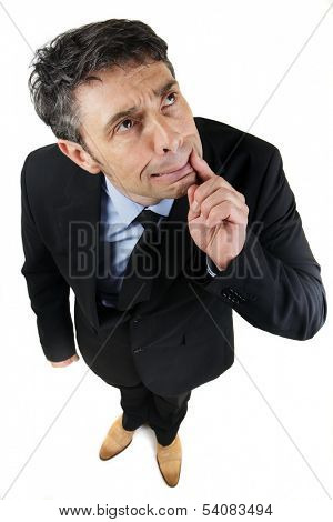 High angle full length portrait of a thoughtful frowning businessman standing looking up with his finger to his mouth as he tries to remember a forgotten fact or find a solution, on white