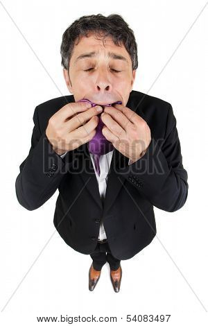 Fun conceptual high angle full length portrait of a stylish business man standing looking up with his eyes closed eating his tie, isolated on white