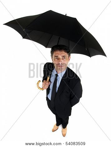 High angle full length portrait of an attractive dapper businessman sheltering under a large black umbrella looking up at the sky with a watchful perplexed expression, on white