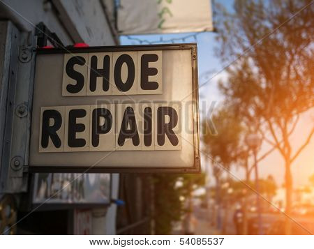 Shoe Repair service sign on city street.