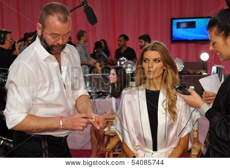 NEW YORK NY - NOVEMBER 13:Makeup Artist Dick Page applying make-up to Maryna Linchuk backstage