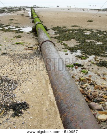 Iron Storm Water Pipe On The Beach Leading Into Sea