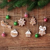 foto of gingerbread house  - Gingerbread cookies hanging over wooden background - JPG