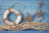 foto of fishnet  - Life buoy decoration on blue shabby background - JPG