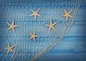 foto of fishnet  - Seastars on the fishing net on a blue background - JPG
