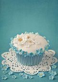 picture of sugarpaste  - Cupcake with white and blue flowers on blue background - JPG