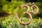 stock photo of sanskrit  - Om statue on the green grass at bokeh background