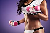 foto of flat stomach  - Woman with flat and sexy stomach working out with a dumbbell - JPG