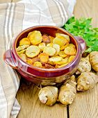 picture of jerusalem artichokes  - Jerusalem artichokes roasted in a clay pot parsley fresh artichoke tubers napkin on a wooden board - JPG