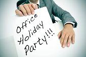 stock photo of office party  - a man wearing a suit sitting in a desk holding a signboard with the text office holiday party written in it - JPG