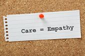 stock photo of empathy  - Care equals Empathy typed on a scrap of paper and pinned to a cork notice board - JPG