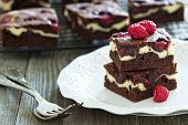 foto of chocolate fudge  - Cheesecake brownies with raspberry stacked on a plate - JPG