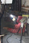 foto of pipe-welding  - A welder welding a flange onto a pipe for a repair on a steam boiler in the background - JPG