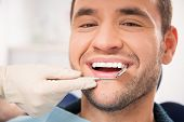 picture of cavities  - Handsome smiling man at doing checkup at dentist - JPG