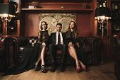 foto of sofa  - Handsome brunette wearing suit sitting on sofa with two beautiful women - JPG