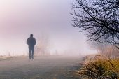 picture of early-man  - A person walk into the misty foggy road in a dramatic sunrise scene with abstract colors - JPG