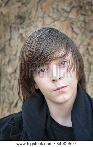 Outdoor Portrait Of A Male Teenager In Front Of A Tree