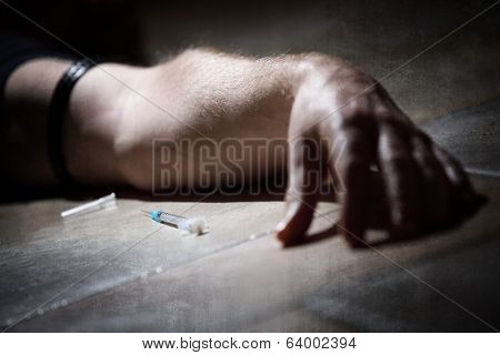 Drug addict with syringe lying down on the floor concept for self harm, shooting up and substance abuse