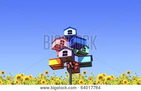 Colorful nesting boxes and sunflowers on blue sky