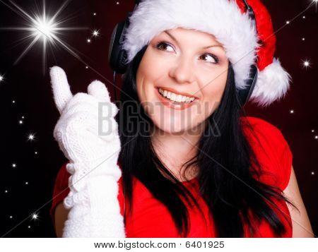 Natal sorridente com fones de ouvido mulher apontando Star