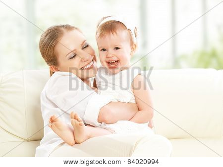 Happy Family. Mother And Baby Daughter Plays, Hugging, Kissing  On The Sofa