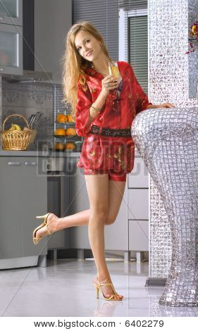 Happy Woman Wearing Red Dress In A Kitchen
