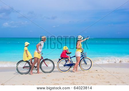Young family with little kids ride bikes on a tropical exotic beach