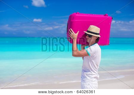Portrait of a young man carrying his luggage on the beach