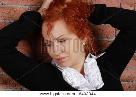 Redheaded Young Woman In Studio Near Brick Wall