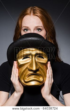 Redhead woman in hat  iwith mask  in hat in hypocrisy consept against grey background